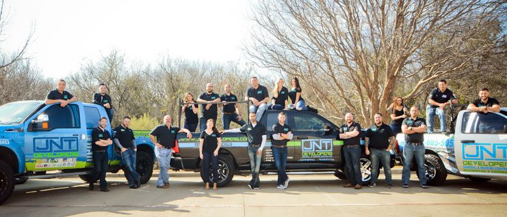 The JNT team all standing around 3 trucks with the the JNT logo on them