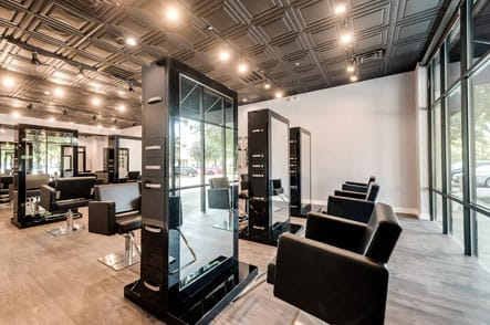 Remodeled salon with large comfortable chairs in front of a mirror
