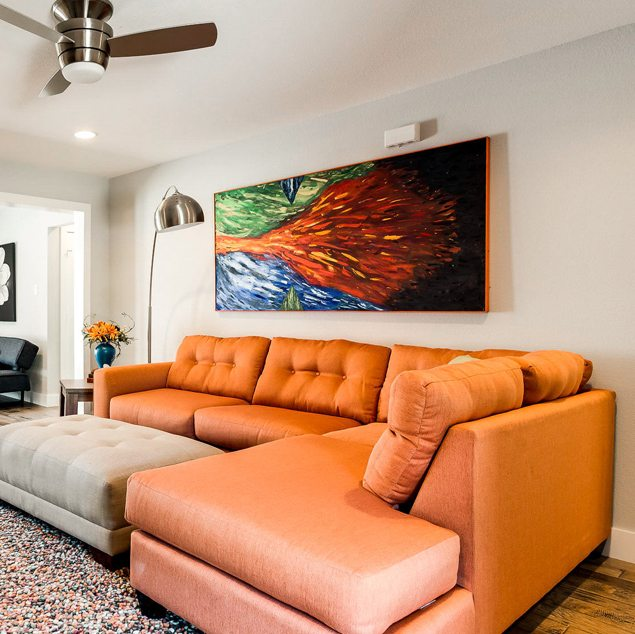 Living room with an orange sofa and a large colorful painting on the wall