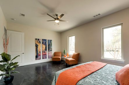 Bedroom with hardwood floor, chairs, ceiling fan and bed with an orange bedspread