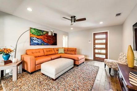 Living room with oranges couches and very modern looking
