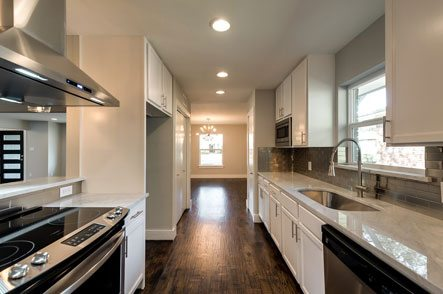 Kitchen with stainless steel hood and range