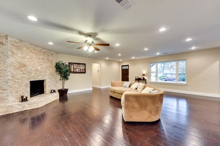 Open living room with ceiling fan and fireplace