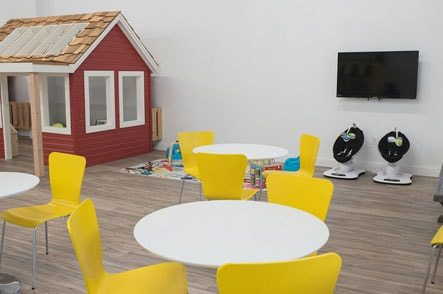 Childs play area with yellow chairs and a white table next to a red playhouse