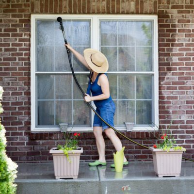 Woman wearing jean short overalls washing her windows with a long wand attached to her hose