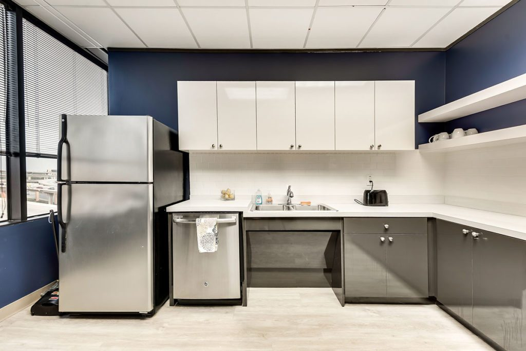 Kitchen with blue walls and white cabinets on top with stainless steel cabinets on the bottom