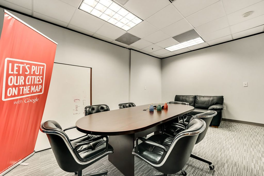 Conference room with wood table and black chairs