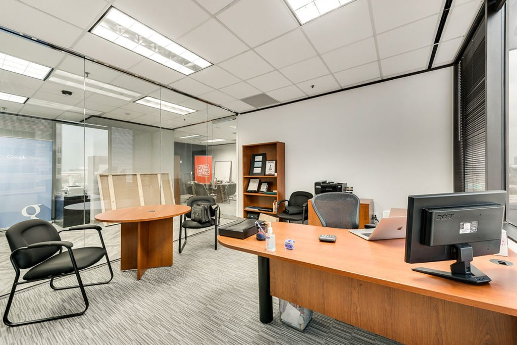 Office with wooden desk, table and bookcase