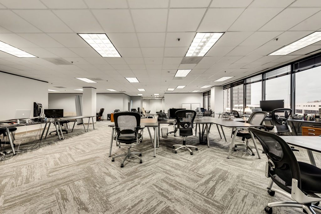 Open office space with multiple desks and black office chairs