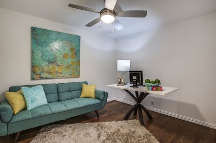 Living room with ceiling fan and mint green couch
