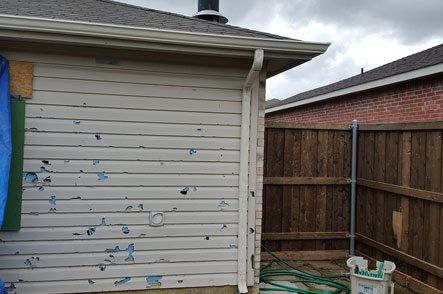 Siding showing heavy storm damage on home